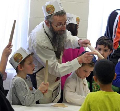 Rabbi Mendel Gurkow teaches students at Shaloh House Chabad in Stoughton how to make matzo, demonstrating rolling pins must be re-sanded after use.